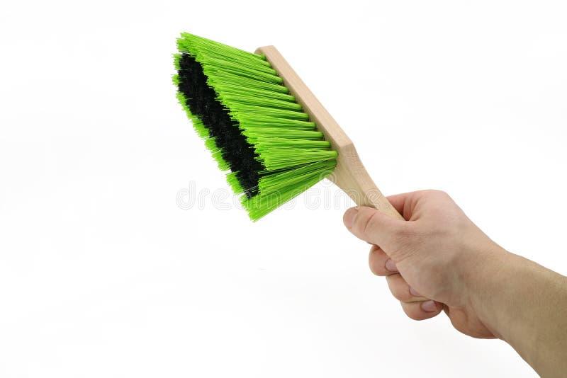 De hand houdt een groene die stofbezem op witte achtergrond wordt geïsoleerd royalty-vrije stock afbeelding