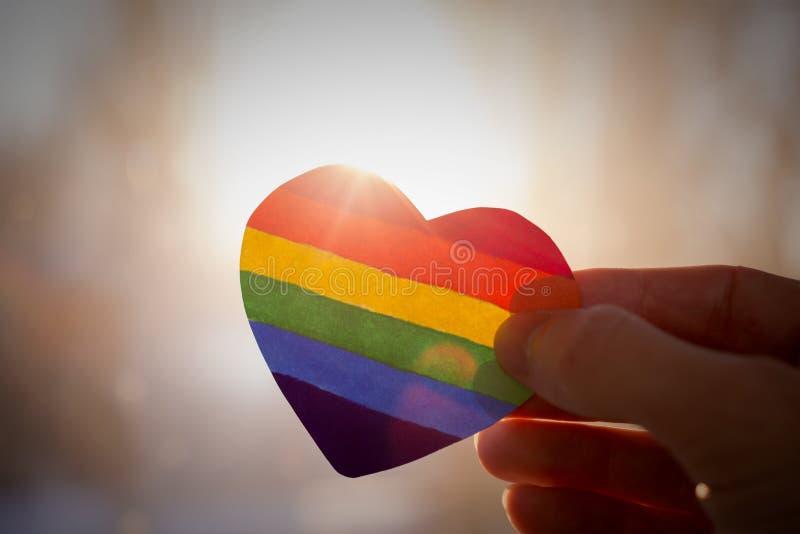 De hand houdt een hart dat als een LGBT-vlag wordt geschilderd royalty-vrije stock afbeeldingen