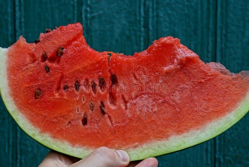De hand houdt een stuk van rode rijpe watermeloen royalty-vrije stock foto