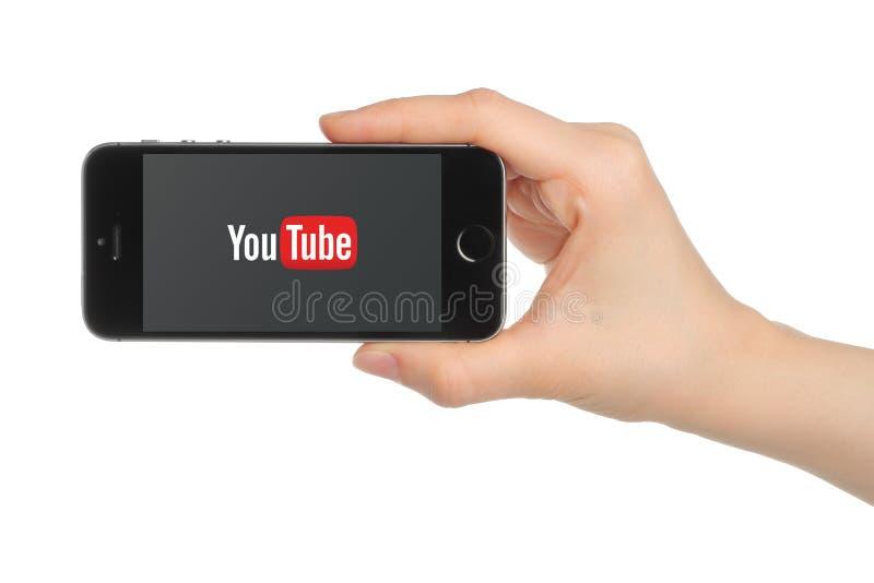 De hand houdt iPhone5s Ruimte met YouTube-embleem op witte achtergrond Grijs royalty-vrije stock fotografie