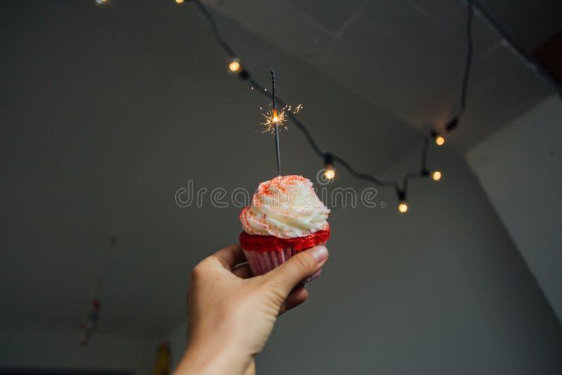 De hand houdt roze zoete cupcake met fonkeling royalty-vrije stock foto's
