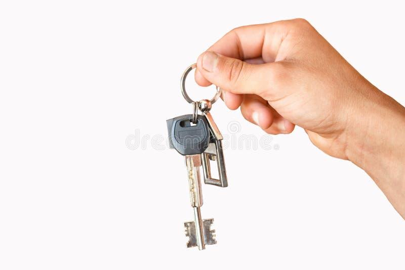 De hand houdt de sleutels aan de flat of het huis stock foto's