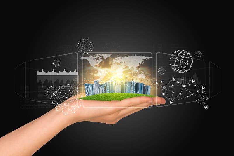 De hand houdt stad van wolkenkrabbers Wereldkaart, grafieken stock foto