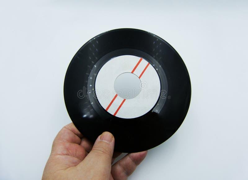 De hand houdt vinyl één enkel verslag op witte achtergrond stock afbeelding