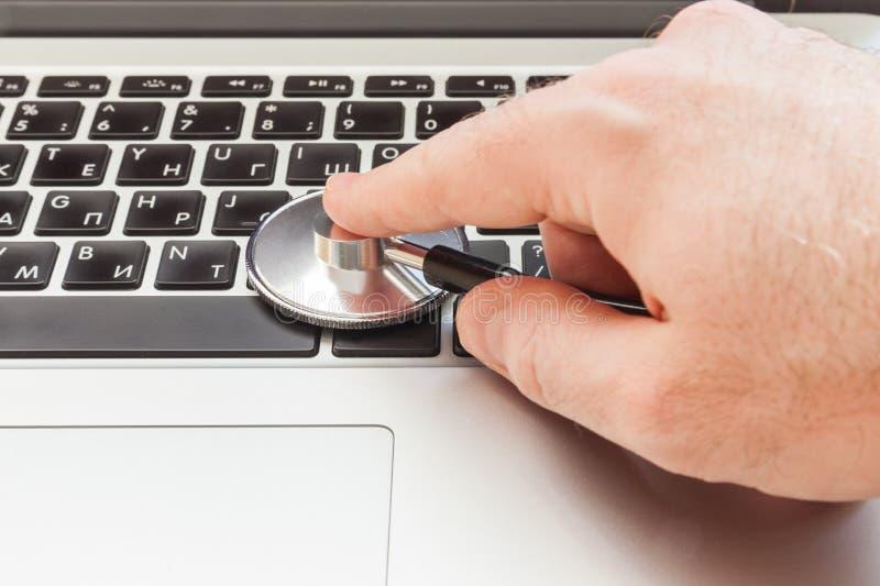 De hand leunt een stethoscoop aan een laptop toetsenbord stock foto