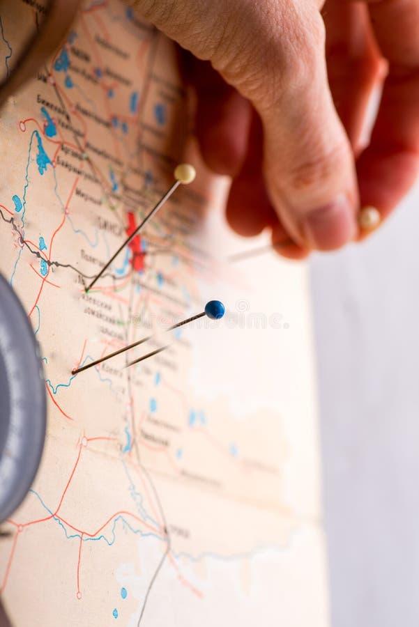 De hand merkt plaatsen op de kaart met spelden stock afbeeldingen