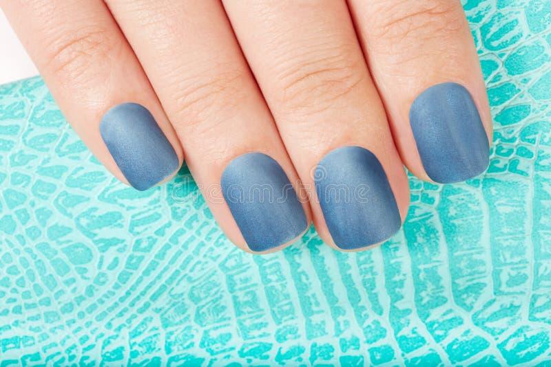 De hand met blauwe steen manicured spijkers royalty-vrije stock afbeelding