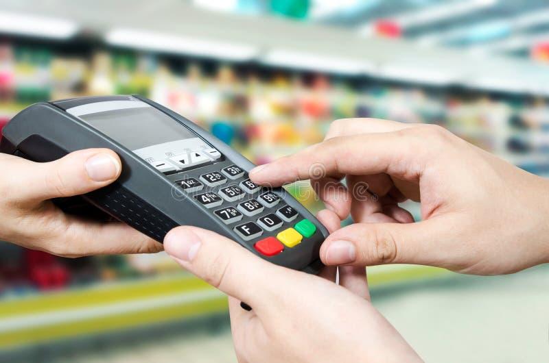 De hand met creditcard jat door terminal voor verkoop stock foto's