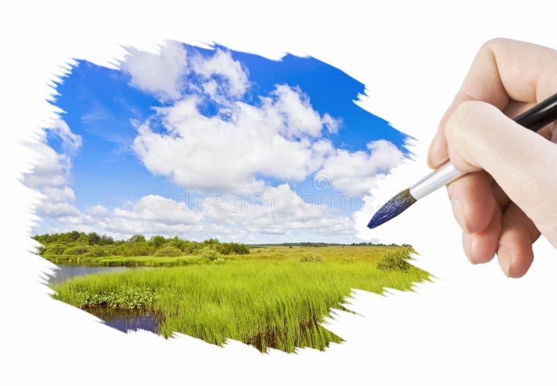 De hand met een borstel schildert een landschap royalty-vrije stock foto