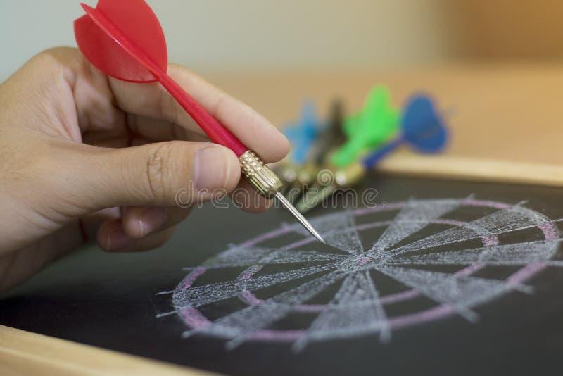 De hand met een pijltje beoogt een dartboard stock fotografie