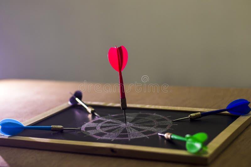 De hand met een pijltje beoogt een dartboard stock foto's