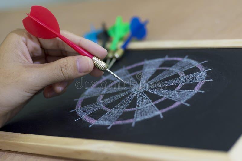 De hand met een pijltje beoogt een dartboard royalty-vrije stock fotografie