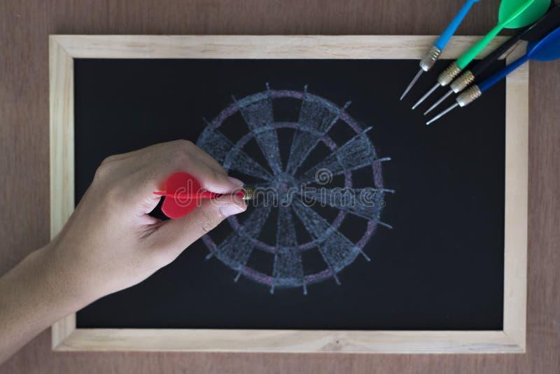 De hand met een pijltje beoogt een dartboard royalty-vrije stock afbeeldingen