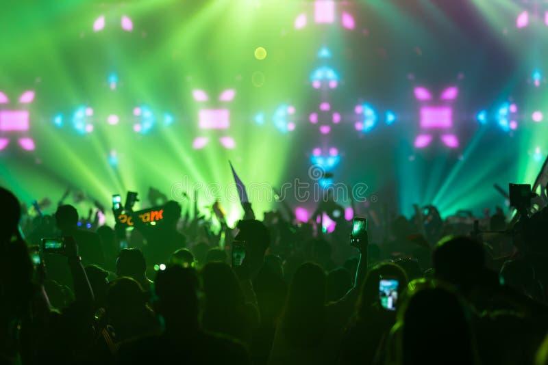De hand met een smartphone registreert levend muziekfestival die foto van van de het overlegmuziek van het overlegstadium de leve stock fotografie