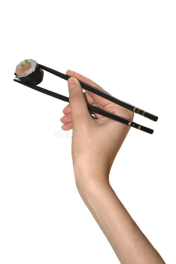 De hand met eetstokje neemt Japanse sushi royalty-vrije stock afbeelding