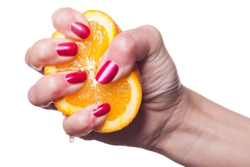 De hand met manicured spijkers raakt een sinaasappel op wit royalty-vrije stock afbeeldingen