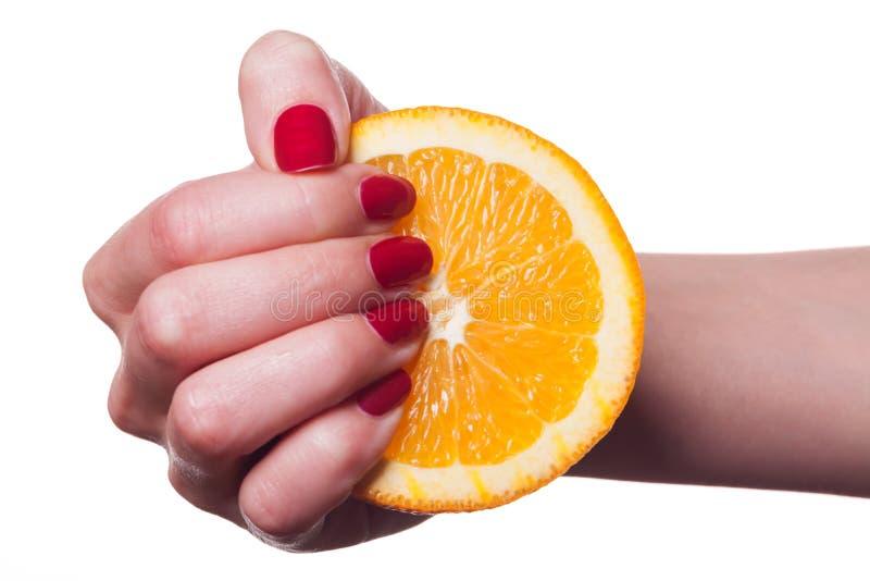 De hand met manicured spijkers raakt een sinaasappel op wit stock afbeelding