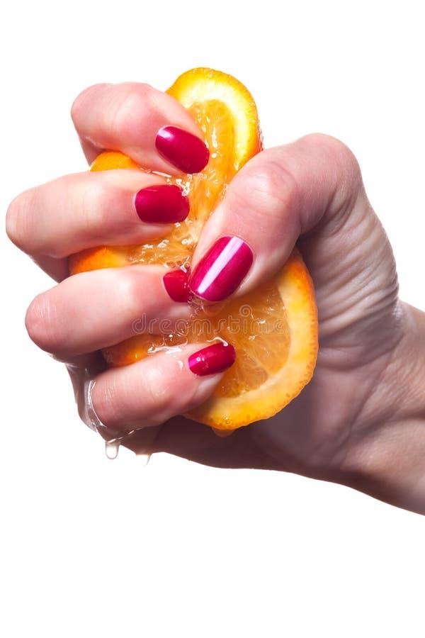 De hand met manicured spijkers raakt een sinaasappel op wit stock afbeeldingen