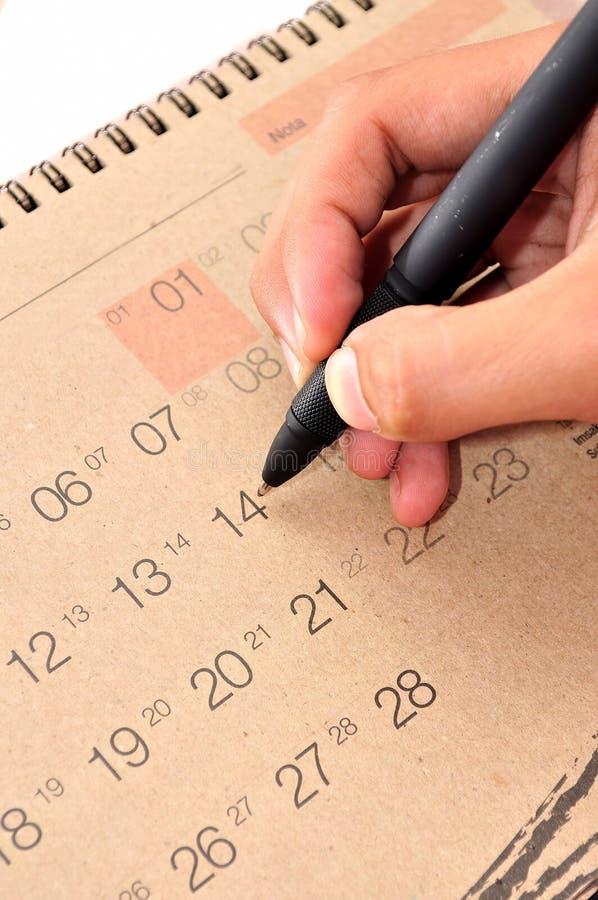 De hand met pen neemt een nota in kalender stock foto's