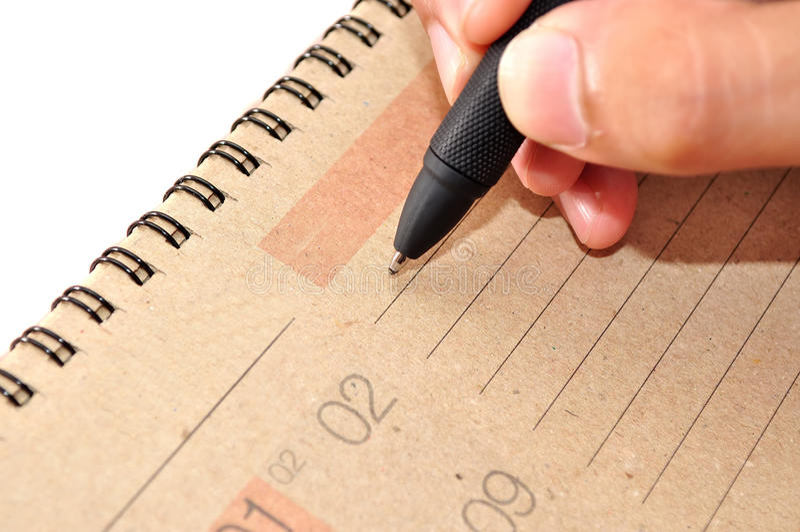 De hand met pen neemt een nota in kalender royalty-vrije stock afbeelding