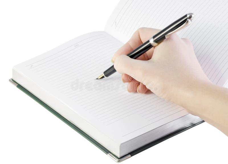 De hand met pen schrijft in notitieboekje royalty-vrije stock afbeeldingen