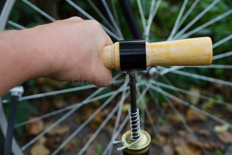 De hand met de pomppompen het wiel van een fiets royalty-vrije stock foto