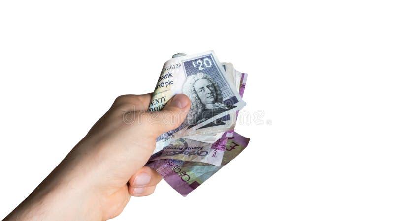 De hand met Schotse geldomkoperij, betaalt contant geld, die geld, corruptieconcept geven stock foto
