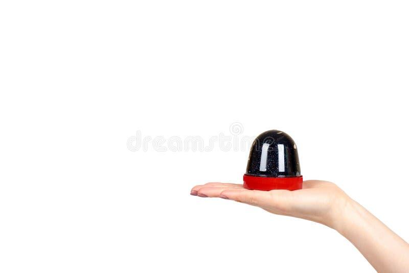 De hand met zwart slijmstuk speelgoed voor jonge geitjes, schittert en goo stock afbeeldingen