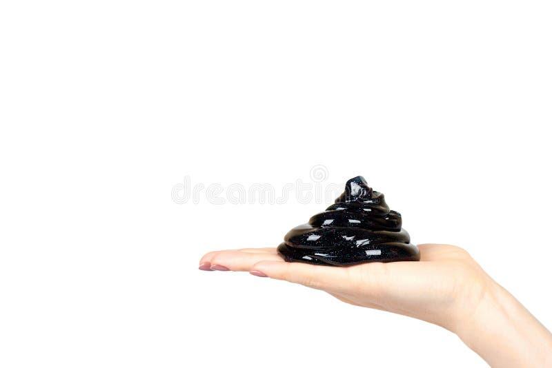 De hand met zwart slijmstuk speelgoed voor jonge geitjes, schittert en goo stock afbeelding