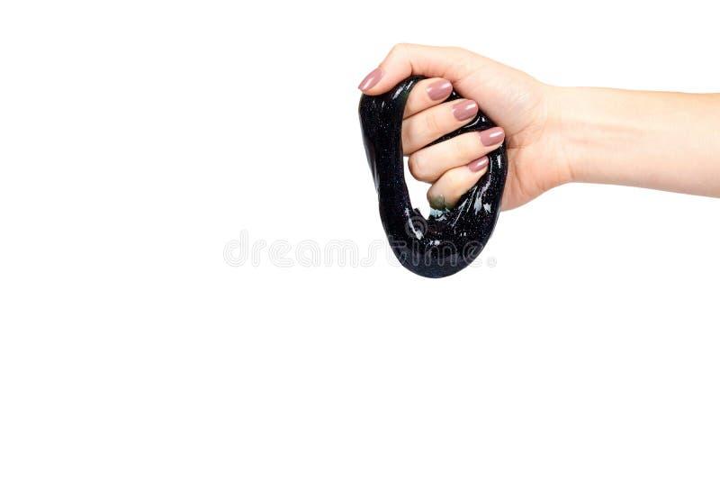 De hand met zwart slijmstuk speelgoed voor jonge geitjes, schittert en goo stock foto