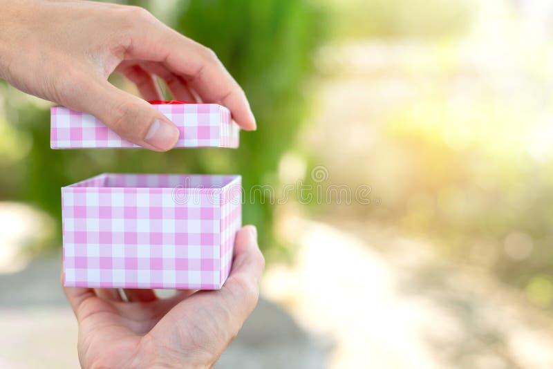 De hand opent de doos op onduidelijk beeldachtergrond stock afbeelding