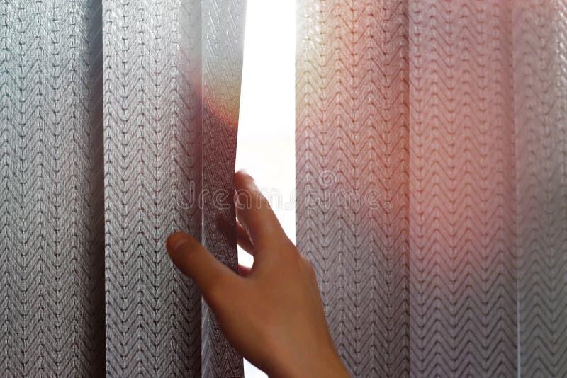 De hand opent zwarte verticale zonneblinden van stof op het venster Sluit omhoog stock afbeeldingen
