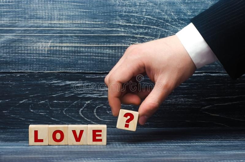 De hand rekt een kubus met het vraagtekensymbool aan de woordliefde uit Het concept liefde en liefdeverhoudingen, loyaliteit en stock foto