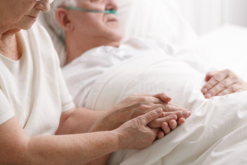 De hand ` s van de huwelijksholding in het ziekenhuis stock afbeeldingen