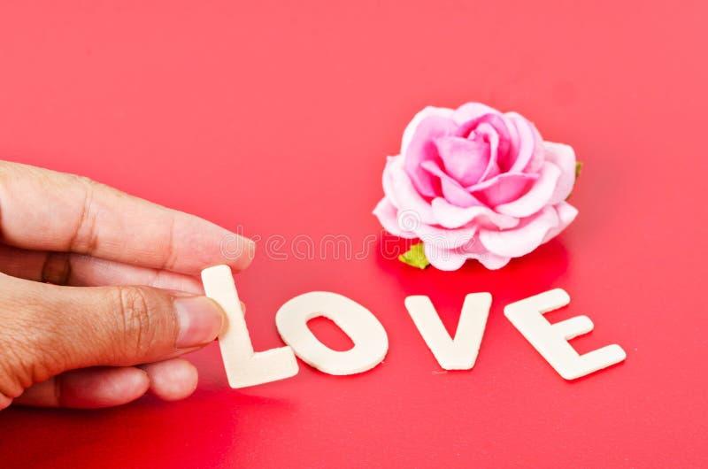 De hand schikt houten brieven als liefdewoord stock afbeeldingen