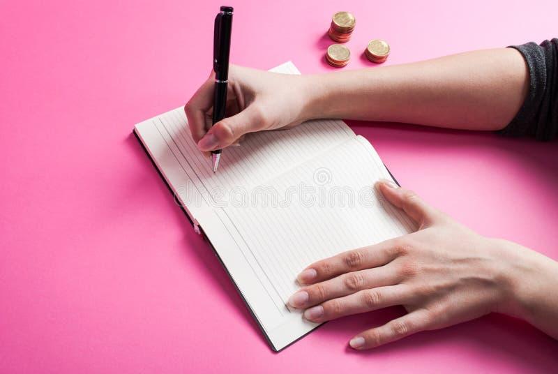 De hand schrijft in notitieboekje en metaalmuntstuk op roze achtergrond royalty-vrije stock afbeelding