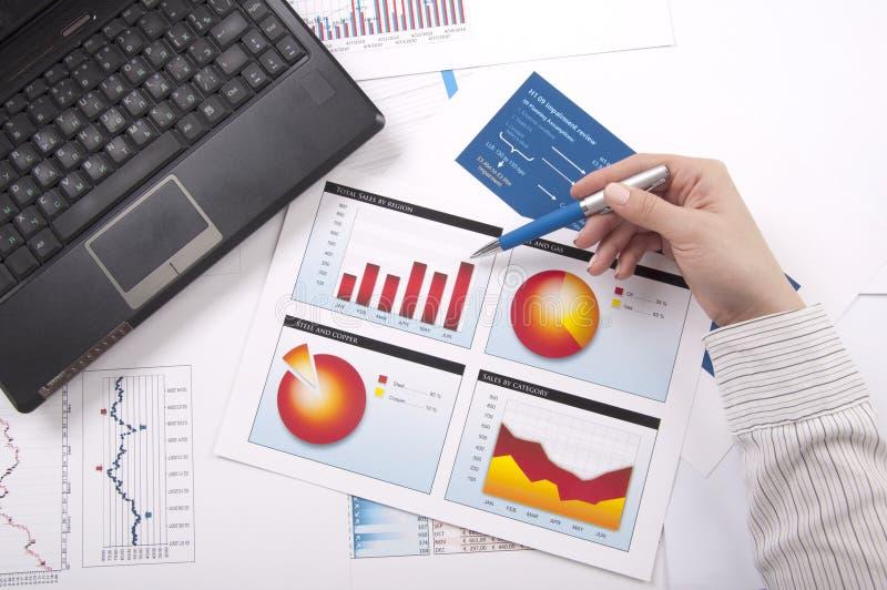 De hand specificeert de financiële grafiek, een werkplaats stock afbeeldingen