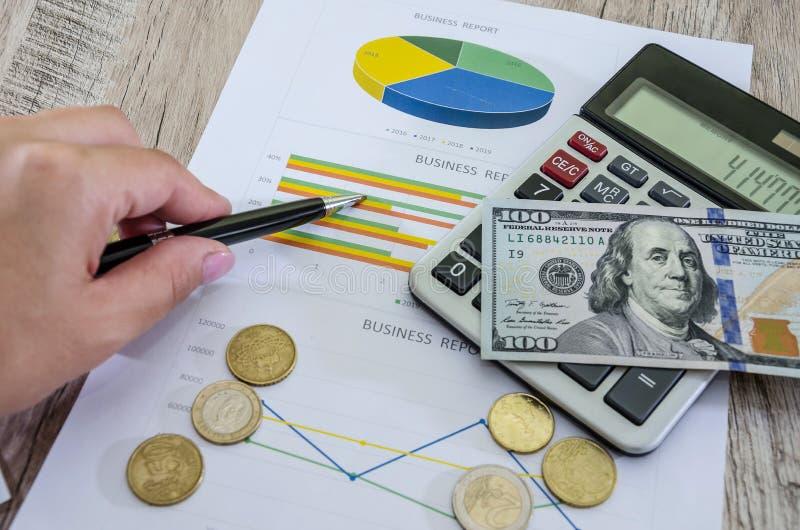 De hand toont op bedrijfsgrafiek, dollars en calculator op de lijst royalty-vrije stock foto's