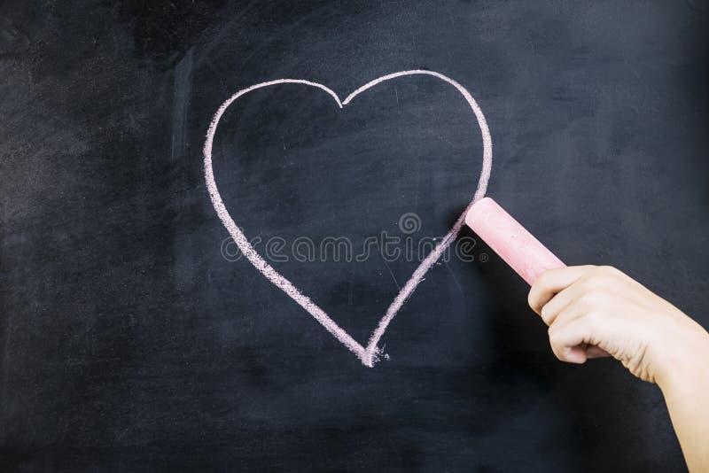De hand trekt een roze krijthart stock foto