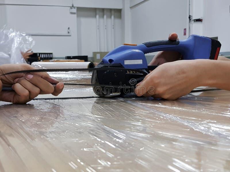 De hand van de arbeider gebruikt de Semi Auto het Vastbinden sh machine, stock fotografie