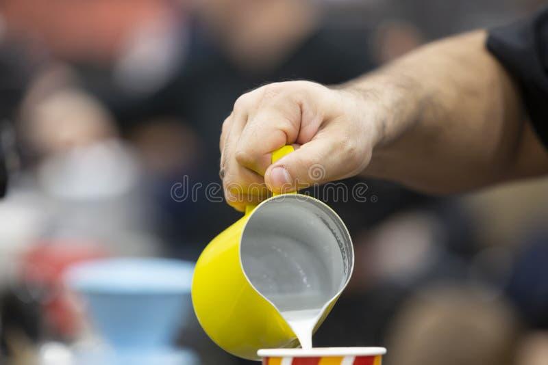 De hand van de barman, giet de milkshake in een glas stock foto