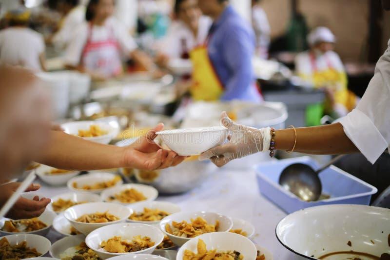 De Hand van de Bedelaars ontvangt liefdadigheidsvoedsel van mede menselijke wezens: het concept het bedelaarsprobleem ter wereld stock foto