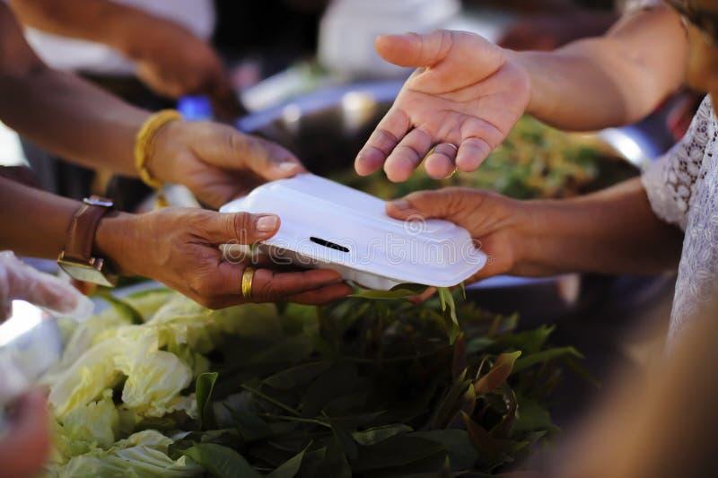 De Hand van de Bedelaars ontvangt liefdadigheidsvoedsel van mede menselijke wezens: Het concept filantropie: De handen van vlucht stock foto's