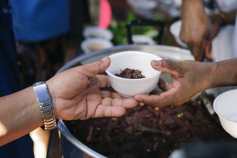 De Hand van de Bedelaars ontvangt liefdadigheidsvoedsel van mede menselijke wezens: Het concept filantropie: De handen van vlucht stock afbeelding
