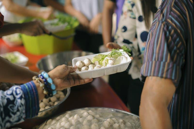 De Hand van de Bedelaars ontvangt liefdadigheidsvoedsel van mede menselijke wezens: Het concept filantropie: De handen van vlucht royalty-vrije stock afbeeldingen