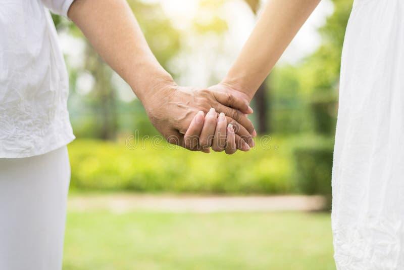 De hand van bejaarden en vrouwenholdingshanden samen, neemt zorg en steun stock afbeelding