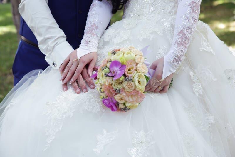 De hand van de bruid op de hand van de bruidegom en een mooi huwelijksboeket op de achtergrond van een wit huwelijkskant kleden z royalty-vrije stock afbeeldingen