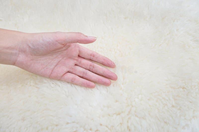 De hand van de close-upvrouw op wit die stoffentapijt van wol geweven achtergrond wordt gemaakt stock afbeeldingen