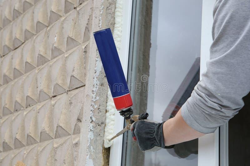 De hand van de arbeider bevestigt een venster door polyurethaanschuim royalty-vrije stock afbeeldingen