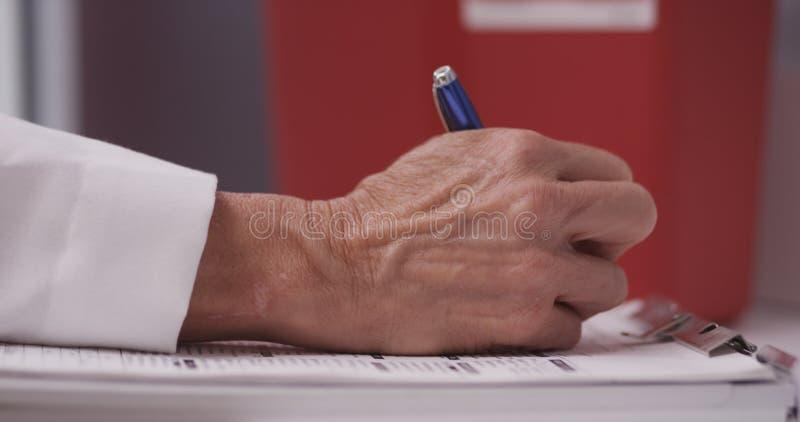 De hand van de arts het schrijven nota's stock afbeelding